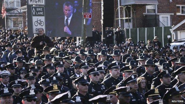 Police turn their backs on New York Mayor Bill de Blasio at a funeral