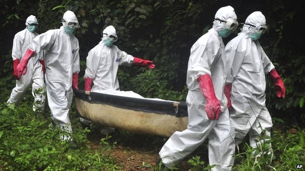 A burial team carry the body of an Ebola victim to a grave in Monrovia, Liberia - 18 October 2014