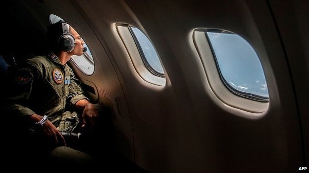 A member of the Indonesian military looks out of the window during a search and rescue operation for missing AirAsia flight QZ8501 - 29 December 2014