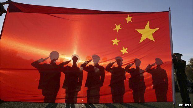 Retired paramilitary policemen, who conduct the daily national flag raising and lowering ceremony on Tiananmen Square, salute to a Chinese national flag during a farewell ceremony in Beijing on 24 November, 2014