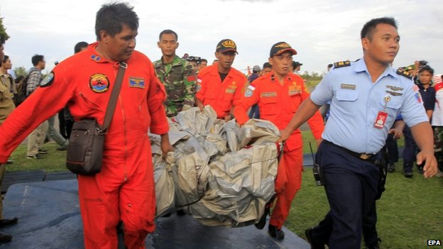 Indonesian air force crew carry what is believed to be slide from missing plane to military base in Pangkalan Bun -
