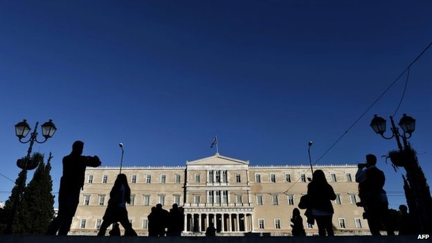 People walk in front of the Greek parliament building in Athens (17 December 2014)
