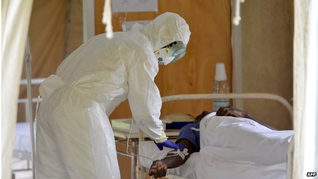 A doctor checks a man in an isolation room on August 14, 2014 at the district hospital of Biankouma.