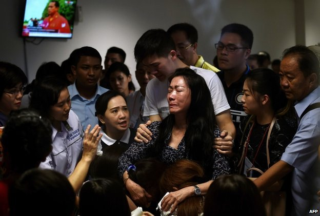 Family members of passengers onboard the missing Malaysian air carrier AirAsia flight QZ8501 react after watching news reports showing an unidentified body floating in the Java Sea, inside the crisis-centre set up at Juanda International Airport in Surabaya on 30 December 2014