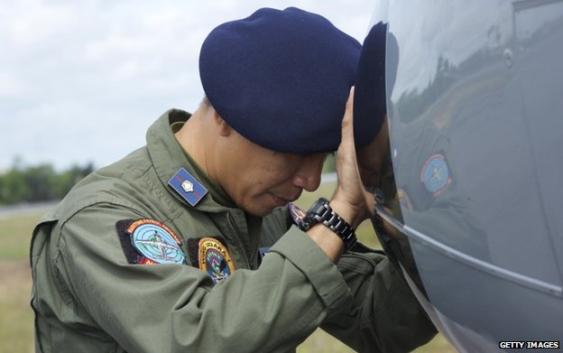 An Indonesian Navy airman prays on his plane before searching the waters near Bangka Island for debris from AirAsia Flight QZ8501 in a navy air patrol craft near Bangka Island, Indonesia, 30 December 2014