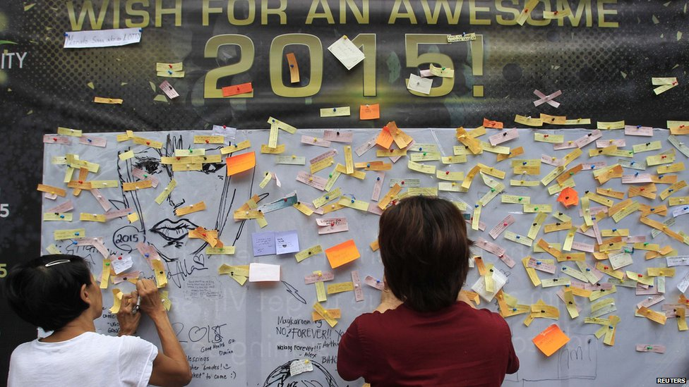 Onlookers write and post their New Year wishes on a wishing wall display at a mall in Quezon city, metro Manila 31 December 2014.