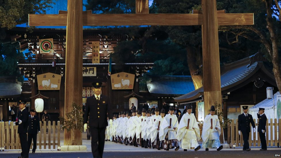 Shinto priests walk through a wooden tore gate after concluding an yearend ritual in preparation for the New Year at the Meiji Shrine in Tokyo, Japan, 31 December 2014.