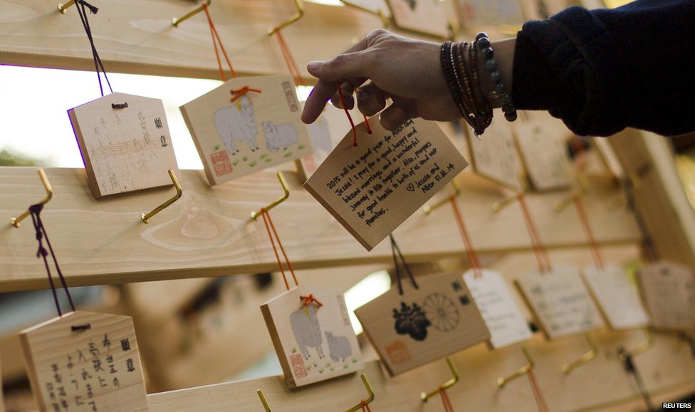 A man hangs a wooden plaque with people's wishes or prayers on a hook during ceremonies bidding farewell to 2014, at the Meiji Shrine in Tokyo on 31 December 2014