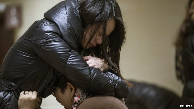 Relatives of a victim hug as they wait at a hospital where injured people of a stampede incident are treated in Shanghai, 1 January 2015