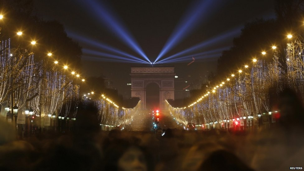 Revellers gather near the Arc de Triomphe on the Champs-Elysees Avenue in Paris (31 December 2014)