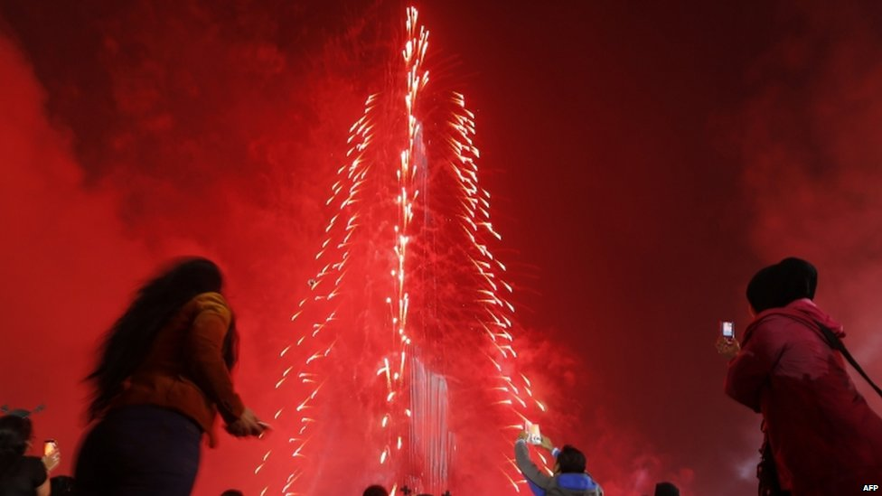 "People watch as Dubai celebrates the new year with a light and sound extravaganza at midnight at the Burj Khalifa, the world""s tallest tower (31 December 2014)"