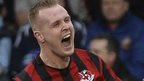 Crusaders striker Jordan Owens runs away in delight after scoring in the first minute against Linfield at Seaview on New Year's Day