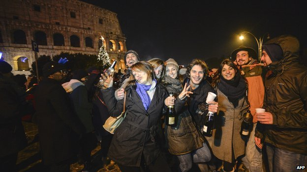 People celebrate in front of the Colosseum in Rome on New Year's Eve