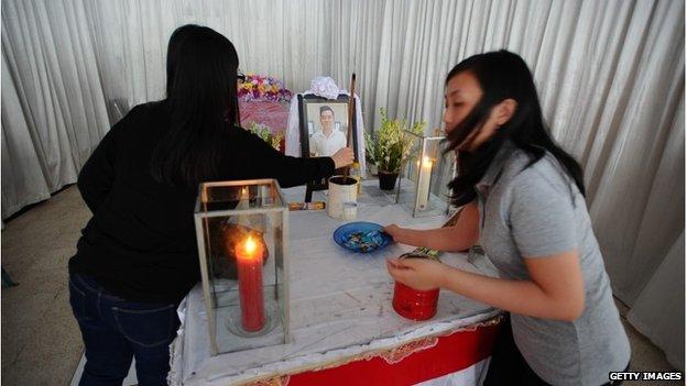 Sisters of AirAsia crash victim Hendra Gunawan Syawal pray near their brother's coffin in Surabaya, Indonesia, 3 January 2015