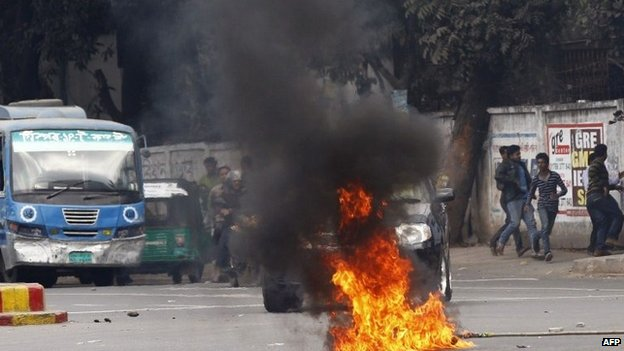 Bangladeshi activists run past burning material on a road close to the home of opposition leader Khaleda Zia in Dhaka on January 5, 2015.