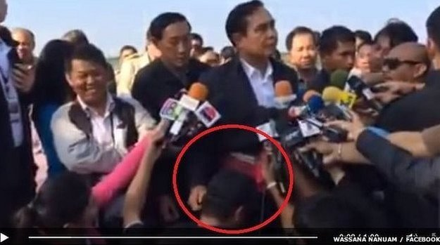 Prime Minister Prayuth Chan-Ocha's hand pats the head of a journalist kneeled in front of him throughout a press briefing