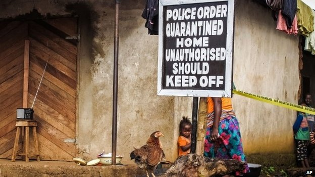 A child stands near a sign advising of a quarantined home in an effort to combat the spread of the Ebola virus in Port Loko, Sierra Leone (22 October 2014)