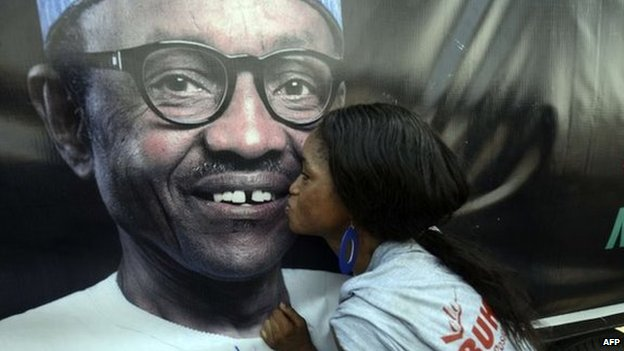 A party member kisses a poster depicting former military ruler and presidential aspirant of the opposition All Progressives Congress (APC) Muhammadu Buhari