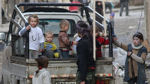 Syrian children stand in the back of a truck as they flee the contested Bab al-Hadid neighbourhood of the northern Syrian city of Aleppo following an overnight rocket attack on January 2, 2015