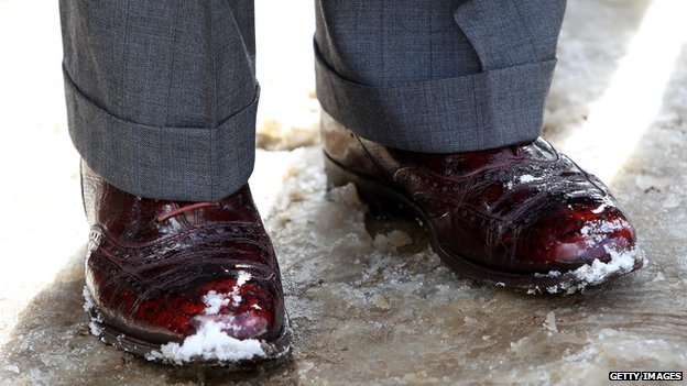 A close-up of a man's shoes in the snow