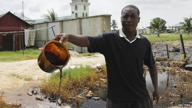 A villager shows a bucket of of crude oil spill at the banks of a river, after a Shell pipeline leaked, in the Oloma community in Nigeria's delta region on 27 November 2014.