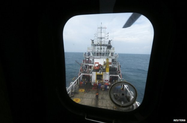 A Russian search and rescue ship is seen through the window of a Super Puma helicopter during a search operation for passengers onboard AirAsia Flight QZ8501, off the Java sea, in Indonesia January 7, 2015