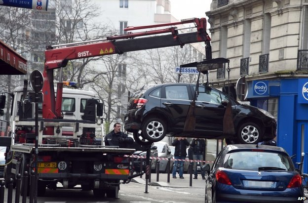 A truck tows the car used by armed gunmen who stormed the Paris offices of satirical newspaper Charlie Hebdo, killing 12 people, on 7 January 2015 in Paris.