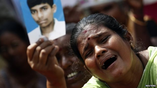 A Tamil woman cries as she hold up an image of her disappeared family member at a protest in Jaffna, August 27, 2013
