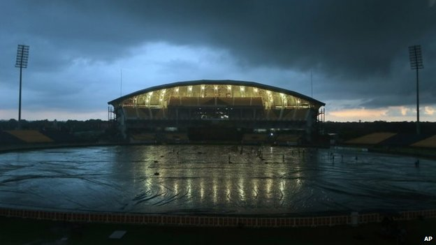Clouds hover over illuminated Mahinda Rajapaksa International Cricket Stadium as ground crew cover the field from rain in Hambantota, Sri Lanka, Tuesday, Dec. 2, 2014