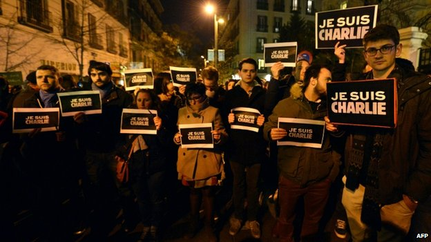 "People hold placards reading ""I am Charlie"" during a gathering in support of the victims of the terrorist attack on French satyrical newspaper Charlie Hebdo, in front of French Embassy in Madrid, on January 7, 2015"