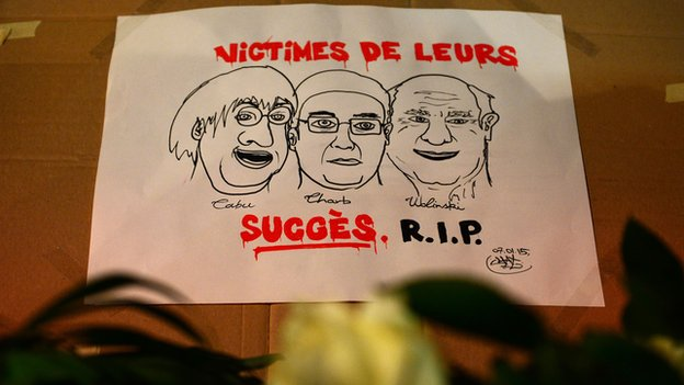 Flowers are placed around a poster depicting killed French cartoonists Cabu, Charb and Wolinski