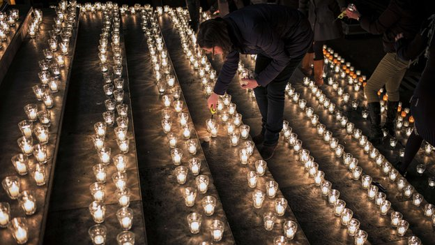 A woman lights a candle during a gathering in Lyon