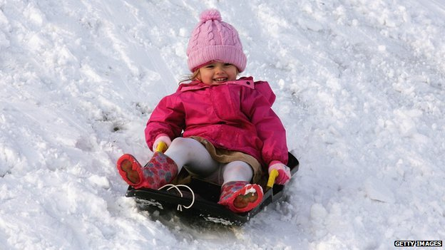 A young girl rides a sled.