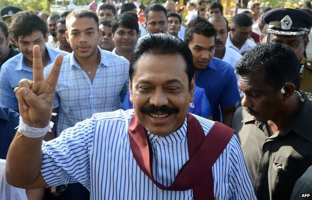 Mahinda Rajapaksa (C) flashes the victory sign outside a polling station in his native town of Tangalla on January 8