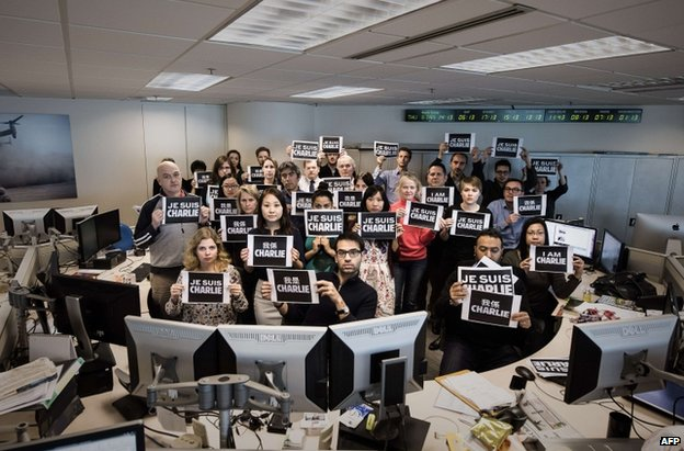 "AFP staff hold up ""I am Charlie"" placards at the French news agency's Hong Kong office, 8 January"