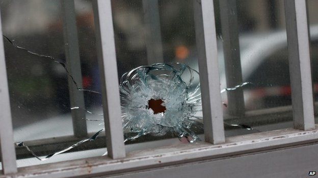 "A bullet impact is seen in a window of a building next to the French satirical newspaper Charlie Hebdo""s office, in Paris, Wednesday, Jan. 7, 2015"