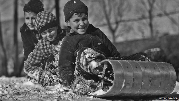 Three children sled in a 1940 photograph.