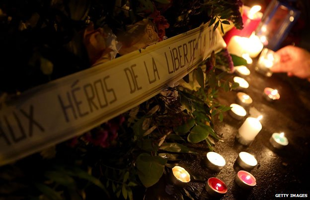 Flowers and candles laid close to the Charlie Hebdo offices