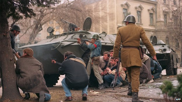 A historical photo of armed civilians and soldier taking cover behind a tank during the Romanian revolution