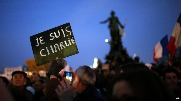 "A demonstrator holds a sign reading ""I am Charlie"" at Place de la Nation during a rally in Paris, 11 January 2015"