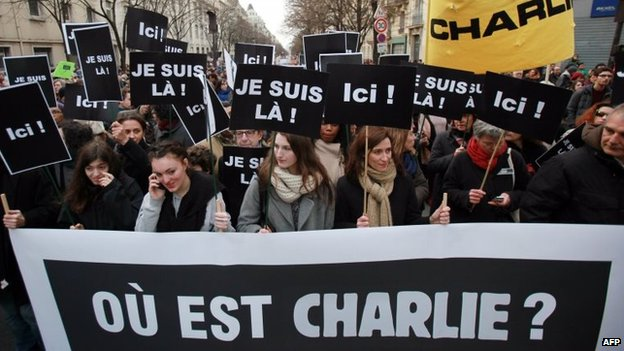"People walk behind a banner reading ""Where is Charlie?"" holding placards reading ""I am here"" take part in a Unity rally Marche Republicaine at the Place de la Republique in Paris, 11 January 2015"