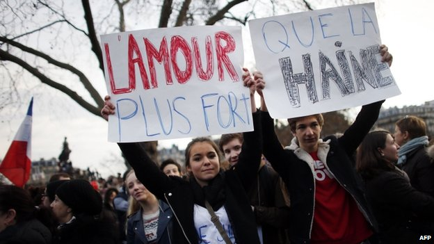 """Youths hold cardboards reading """"Love is stronger than Hate"""" during the unity rally"""