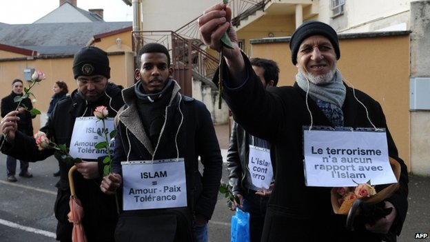 """Muslims with a sign reading """"Islam is against terrorism"""" and """"Terrorism has nothing to do with Islam"""" gesture during a demonstration against fanaticism in the Sablons neighborhood of Le Mans, western France (10 January 2015)"""