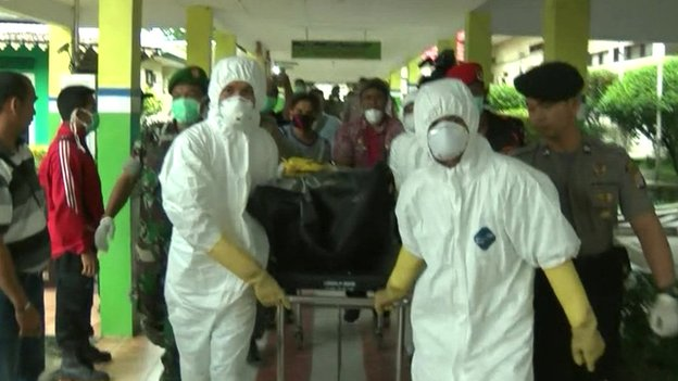 Workers transporting bodies from AirAsia crash