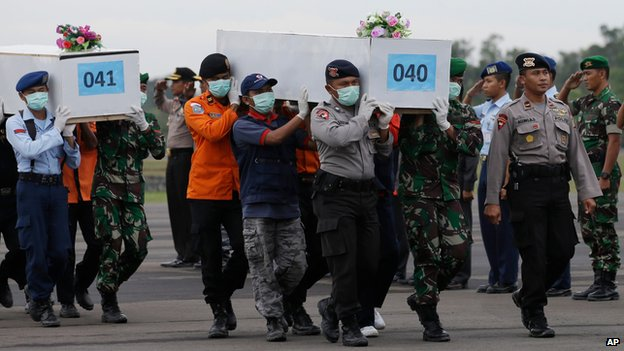 Indonesian  officials carry bodies at Pangkalan Bun airport