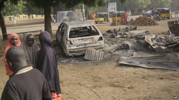 Children stand near the scene of an explosion in a mobile phone market in Potiskum, Nigeria, on 12 January  2015