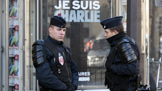 French police stand close to a sign that reads 'Je Suis Charlie' (I am Charlie), referring to Charlie Hebdo, the satirical magazine whose Paris offices were attacked by brothers, French nationals Cherif and Said Kouachi last week, on January 11, 2015