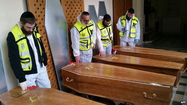 Zaka emergency response members stand next to the coffins of the four French Jews killed in the Paris attacks