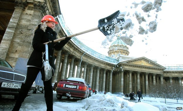 A woman shovels snow in St Petersburg