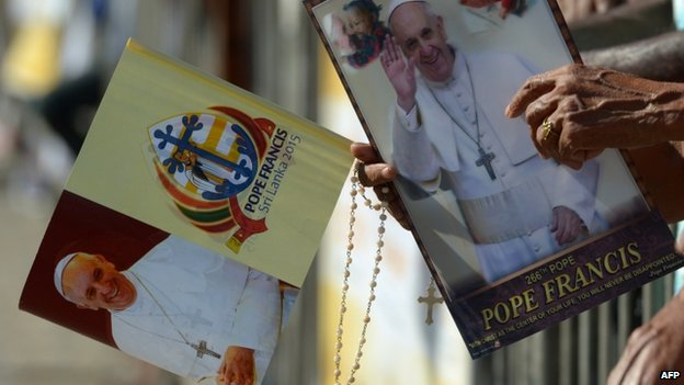 Sri Lankan Christians hold paraphernalia bearing the portrait of Pope Francis as they wait for his arrival in Colombo